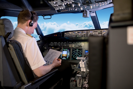 Young male pilot sitting on seat reading instructions in cockpitの写真素材 [FYI02239083]