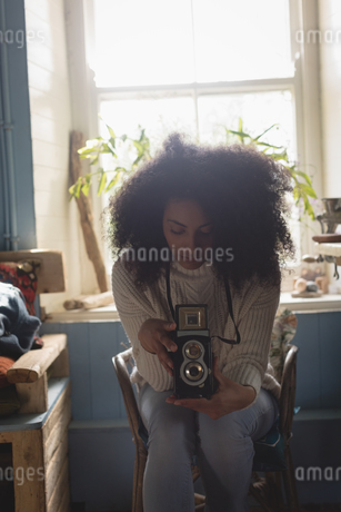 Woman looking at pictures on vintage camera at homeの写真素材 [FYI02239113]