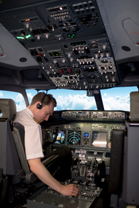 Male pilot switching controls in cockpitの写真素材 [FYI02239128]
