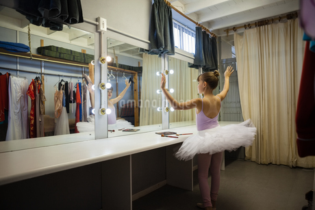 Rear view of girl practicing ballet dance while reflecting on mirrorの写真素材 [FYI02239138]