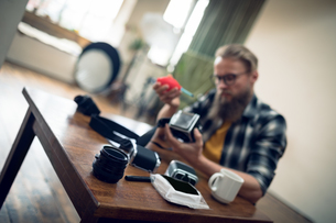 Photographer cleaning camera while sitting at tableの写真素材 [FYI02239139]