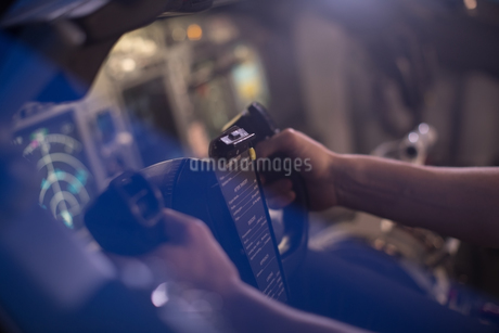 High angle view of pilot holding steering wheel in cockpitの写真素材 [FYI02239220]