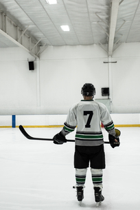 Rear view of male player holding ice hockey stickの写真素材 [FYI02239236]