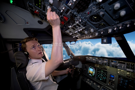 Side view of young male pilot switching controls in cockpitの写真素材 [FYI02239243]
