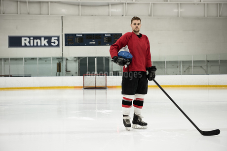 Portrait of ice hockey player holding helmet and stickの写真素材 [FYI02239260]