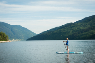 Side view of woman paddleboarding in lakeの写真素材 [FYI02239294]