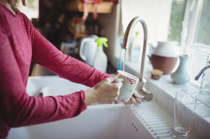 Woman washing a mug in kitchenの写真素材 [FYI02239301]