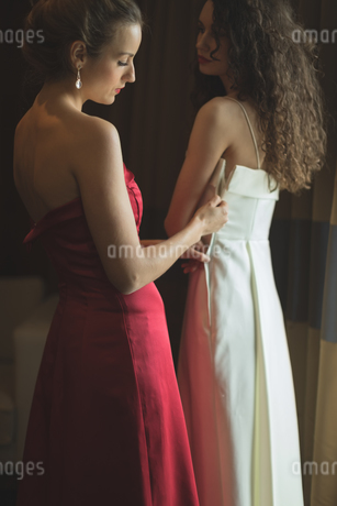 Bridesmaid assisting bride to dressの写真素材 [FYI02239307]