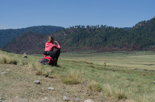 Rear view of female hiker sitting on rockの写真素材 [FYI02239327]