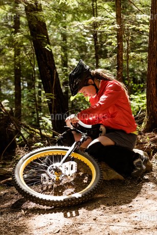 Young woman adjusting unicycle while sitting on rockの写真素材 [FYI02239348]