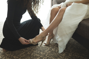 Bridesmaid helping bride to put on wedding shoesの写真素材 [FYI02239382]