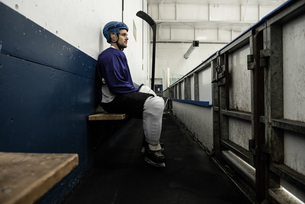 Ice hockey player on seat at corridorの写真素材 [FYI02239389]