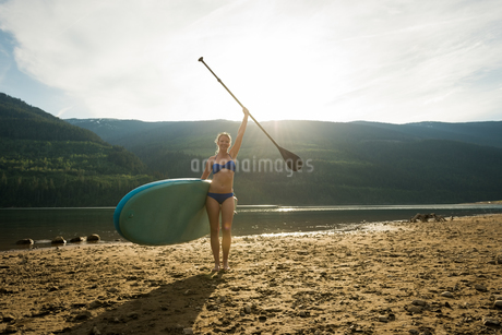 Portrait of smiling young woman standing with paddleboard and oar at lakeshoreの写真素材 [FYI02239403]