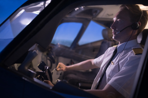 Handsome young male pilot flying airplaneの写真素材 [FYI02239434]