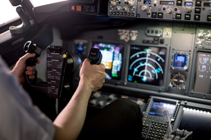 Cropped image of male pilot holding steering wheel in cockpitの写真素材 [FYI02239467]