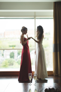 Bride showing wedding ring to bridesmaidの写真素材 [FYI02239484]