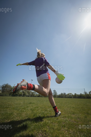 Rear view of woman playing soccer on sunny dayの写真素材 [FYI02239496]