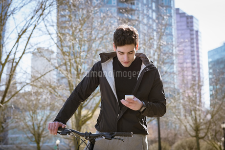 Young man using mobile phone while standing by bicycleの写真素材 [FYI02239532]