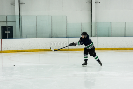 Full length of player playing ice hockeyの写真素材 [FYI02239536]