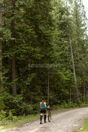 Rear view of woman walking with unicycle on dirt roadの写真素材 [FYI02239555]