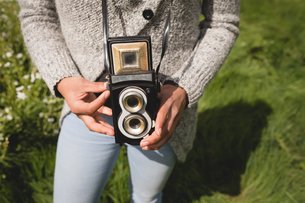 Mid-section of woman holding vintage cameraの写真素材 [FYI02239614]