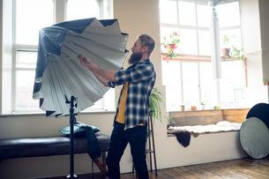 Side view of photographer adjusting umbrellaの写真素材 [FYI02239618]