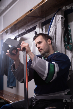 Male player taping hockey stick and puck in locker roomの写真素材 [FYI02239644]