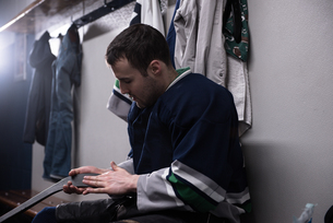 Player holding hockey stick in locker roomの写真素材 [FYI02239649]