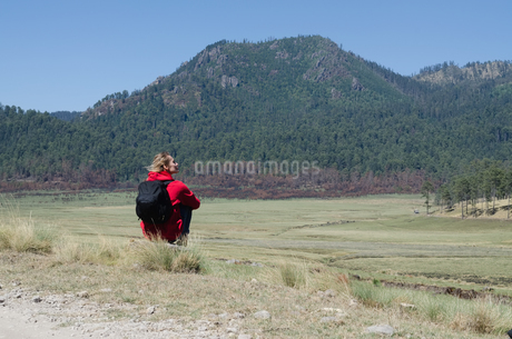 Rear view of female hiker with backpack sitting on fieldの写真素材 [FYI02239657]