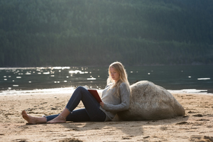 Woman reclining on rock while reading novelの写真素材 [FYI02239663]