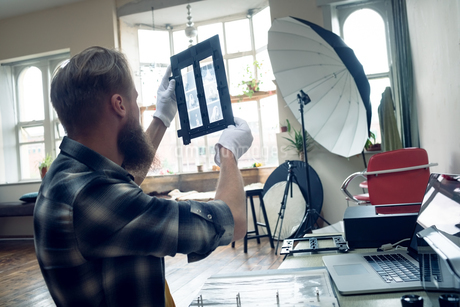 Side view of photographer looking at negatives in frameの写真素材 [FYI02239668]