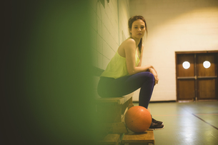 Side view portrait of female basketball player on benchの写真素材 [FYI02239674]