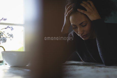 Stressed woman sitting in the living roomの写真素材 [FYI02239676]