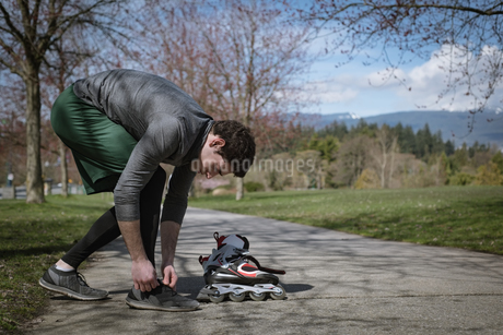 Side view of man tying shoelace while standing by roller skateの写真素材 [FYI02239685]