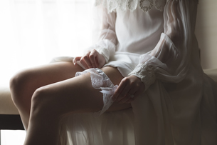 Bride wearing stockings in living room at homeの写真素材 [FYI02239701]