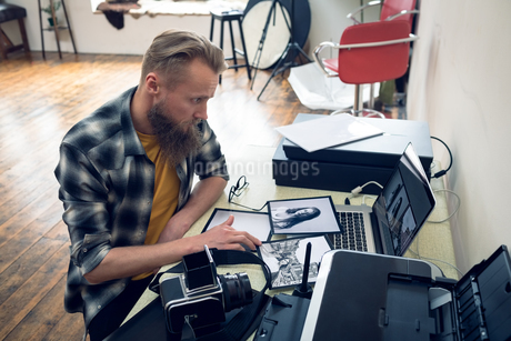 Photographer using laptop while editing photograph on laptopの写真素材 [FYI02239725]
