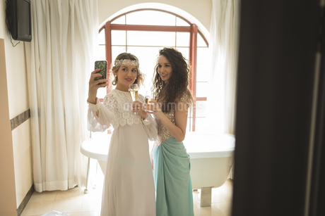 Bride and bridesmaid taking selfie while having champagneの写真素材 [FYI02239740]