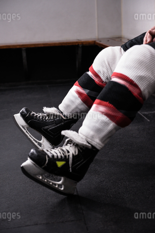 Low section of player wearing ice skates relaxing in dressing roomの写真素材 [FYI02239780]