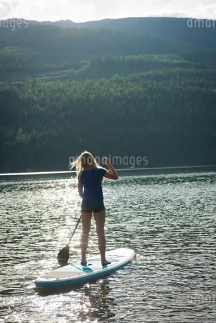 Rear view of woman oaring paddleboard in lakeの写真素材 [FYI02239824]
