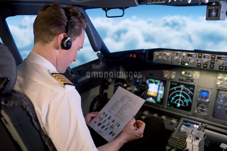 Young male pilot reading instructions while sitting in cockpitの写真素材 [FYI02239826]
