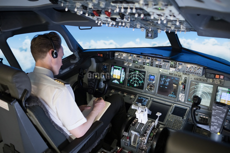 High angle view of young pilot writing on book while sitting in cockpitの写真素材 [FYI02239827]