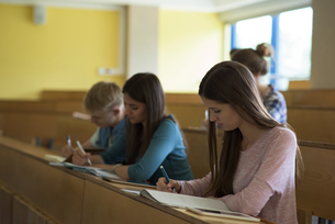 Young college students writing on book at deskの写真素材 [FYI02239831]