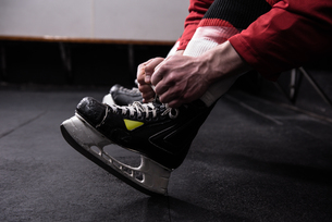 Low section of hockey player tying ice skateの写真素材 [FYI02239834]