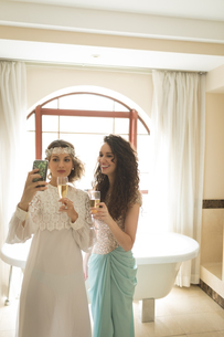 Bride and bridesmaid taking selfie while having champagneの写真素材 [FYI02239860]