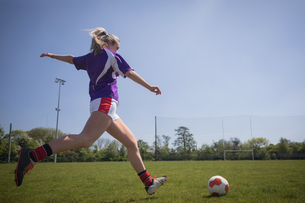 Full length of woman playing soccer on fieldの写真素材 [FYI02239883]