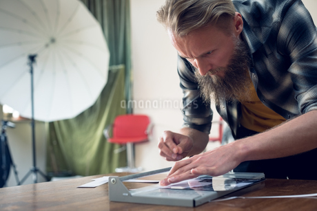Close up of photographer cutting photograph on paper cutting toolの写真素材 [FYI02239891]