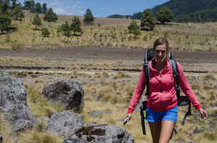 Female hiker with backpack walking on fieldの写真素材 [FYI02239902]