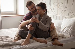 Full length of couple sitting on bed at homeの写真素材 [FYI02239910]