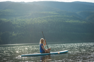 Side view of woman sitting on paddleboard in lakeの写真素材 [FYI02239937]