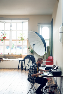 Side view of photographer using graphics tablet while editing at tableの写真素材 [FYI02239966]